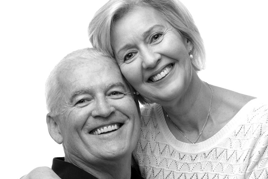 A couple smiling to show off their natural-looking smiles with dental implants.