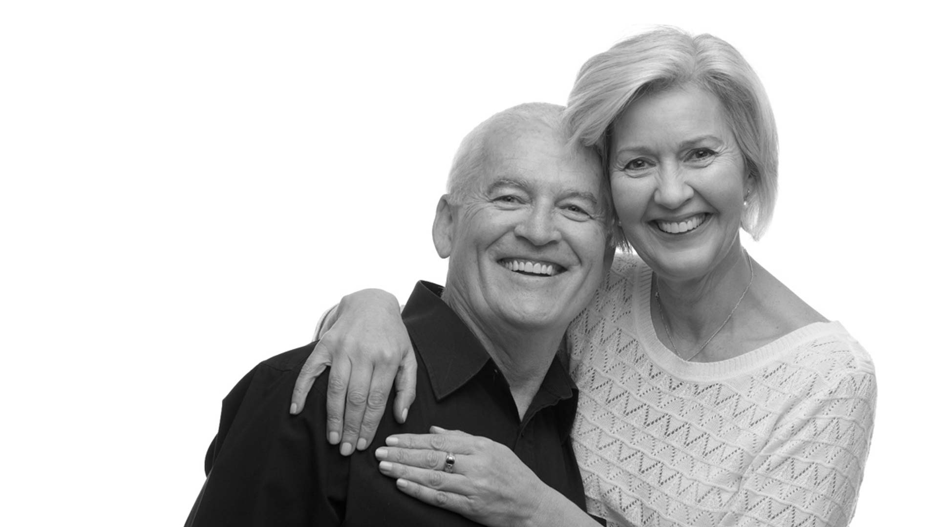 Two patients smiling to show their new smiles restored using All on 4 dental implants.